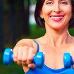 donna con pesi che si allena nel parco