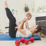 giovane donna che tiene in braccio un bambino mentre fa ginnastica